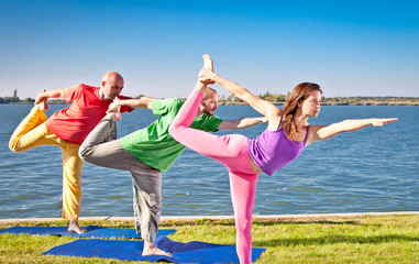 Tree people practice Yoga asana at lakeside. Yoga concept.