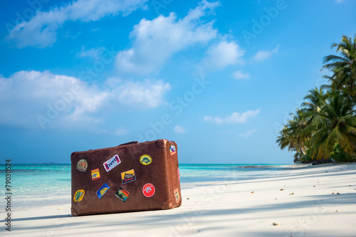 Billede Travel vintage suitcase is alone on a beach