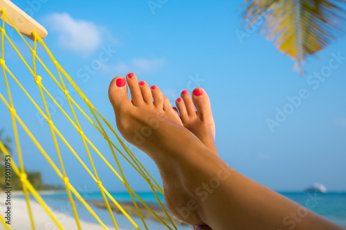 woman feet in hammock on the beach - 79030753