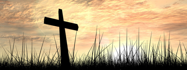 Black cross in grass at sunset