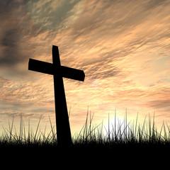Black cross in grass ar sunset