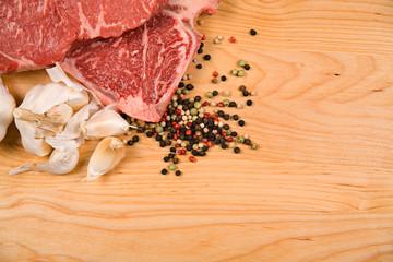 Steak: Raw Steaks with Garlic and Peppercorns