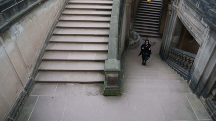Young girl in black clothes escaping the dungeon on the stairs