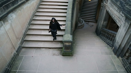 Young girl in black clothes going to dungeon on the stairs