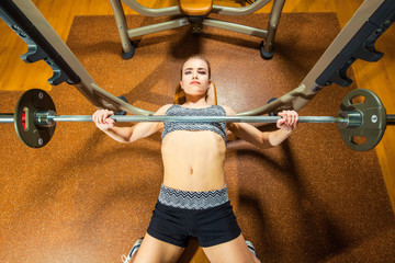 Sports young woman doing exercises with barbell on bench in the