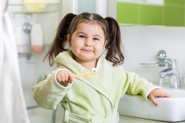 Smiling child brushing teeth