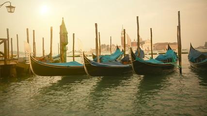 Venetian gondolas at sunrise tied near the pier