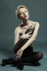 Elegant nude woman with short blond  hair.