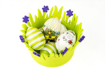 easter painted eggs in green basket made of fabric
