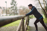 Runner man stretching in a park