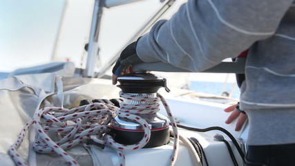 Sailor's hand on a winch of sailing boat