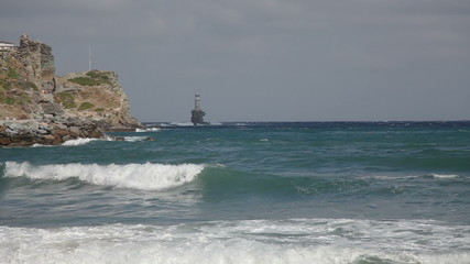 Rock and lighthouse at the stormy sea on greek island Andros