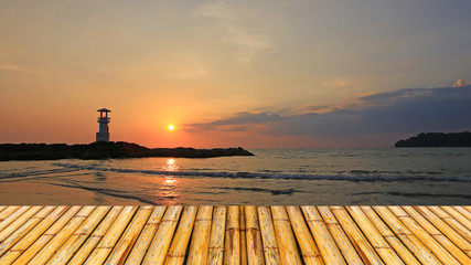 Lighthouse with sunset of thailand sea with  bamboor floor