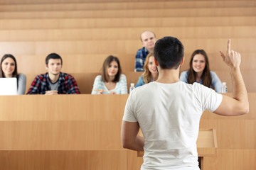 Group of students sitting in classroom and listening speaker