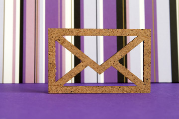 Wooden envelope icon on purple striped background