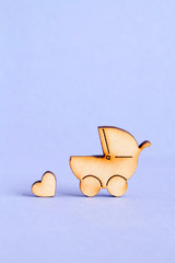 Wooden icon of baby carriage and little heart on purple backgrou
