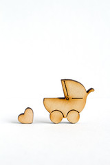 Wooden icon of baby carriage and little heart on white backgroun