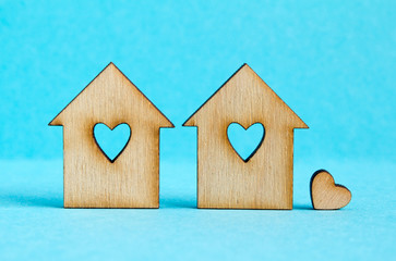 Two wooden houses with hole in the form of heart with little hea