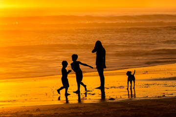 Family beach walk at sunset
