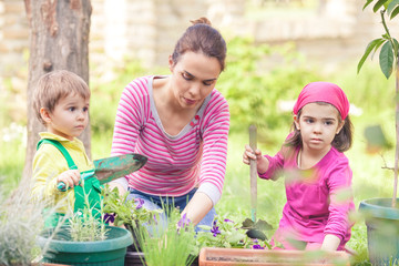Mother gardening with her cute little son and