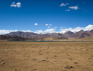Rocky mountains and scorched valley on a background of blue sky