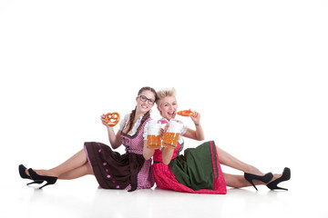 Freundinnen im Dirndl machen Picknick mit Bier und Breze