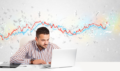 Business man sitting at table with stock market graph