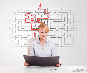 Business woman at desk with labyrinth and arrow