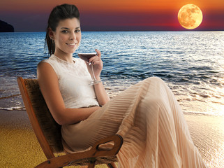 woman with drink sitting on a beach