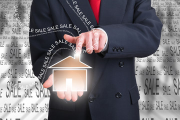 businessman holding an home icon in his hand
