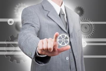 Businessman showing a cogwheel