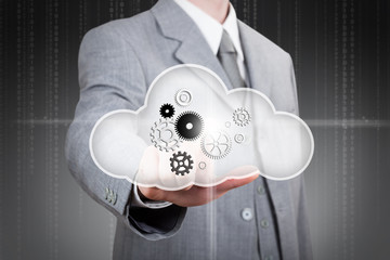 business man pointing at set of gears in the cloud