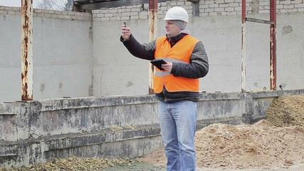 Civil engineer with cell phone near the unfinished building