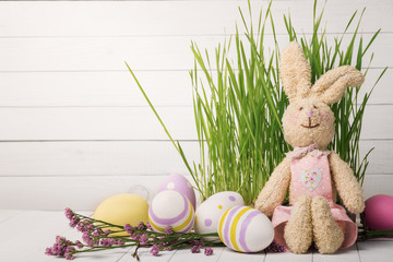 Soft toy in the shape of a rabbit with colorful Easter eggs and