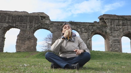 Man eating banana under Roman acqueducts ruins
