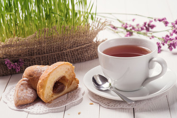 Cup of black tea with a croissant
