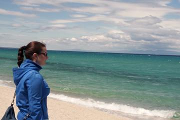 Young beautiful girl looking at sea