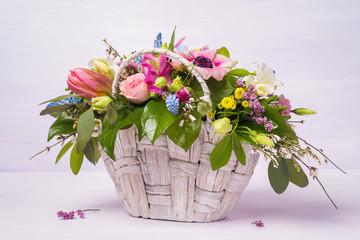 Beautiful bouquet of spring flowers in a wicker basket