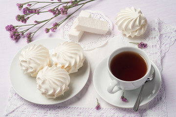 Cup of black tea with marshmallows and fruit candy