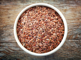 Bowl of flax seeds on old wooden table