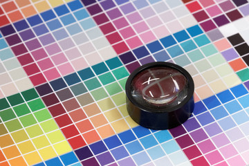 Magnifying glass on colorful test print