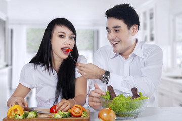 Couple cook and eat salad