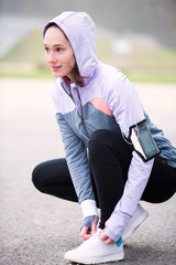 Young attractive woman tying shoelaces before a running session