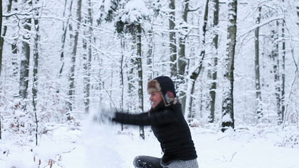 Young woman playing with snow in winter forest, slow motion
