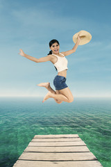 Gorgeous woman with hat jump at pier