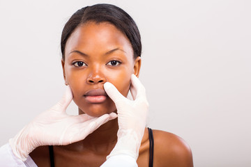 doctor checking african woman lips before plastic surgery