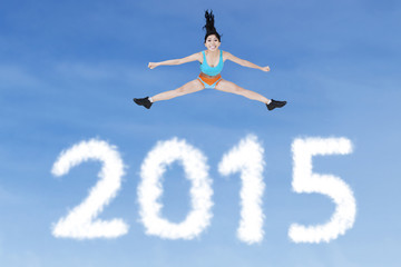 Healthy woman jumping over numbers 2015