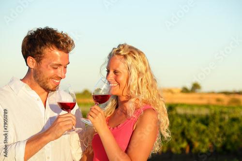 Leinwanddruck Bild Drinking red wine couple at vineyard