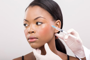 cosmetic doctor injecting african woman face
