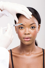 african woman receiving cosmetic injection on her forehead